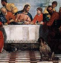 Dog looking at cat which appears under Last Supper table